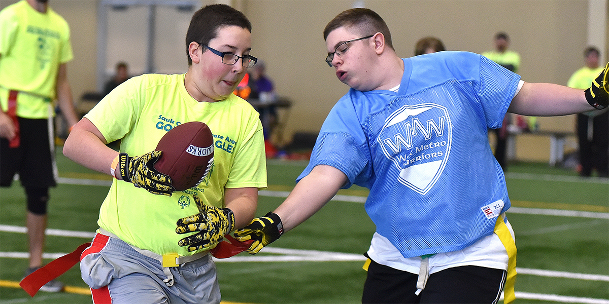 One Special Olympics Minnesota athlete carries a football while another reaches for his flag
