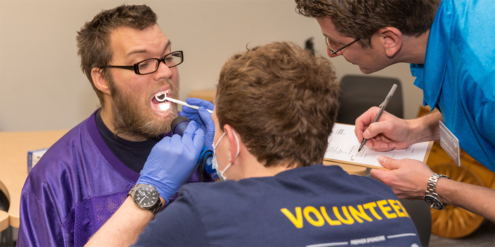 A dental care professional peers into a Special Olympics Minnesota athlete's mouth while another dental hygienist looks on