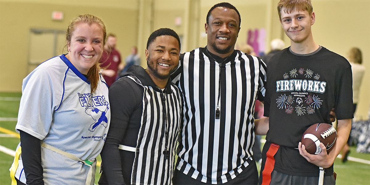 Two Special Olympics Minnesota flag football athletes pose with two referees and smile at the camera